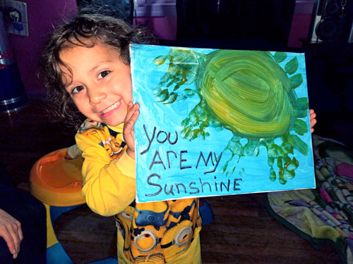 Child proudly shows artwork made during a Parents as Teachers home visit.