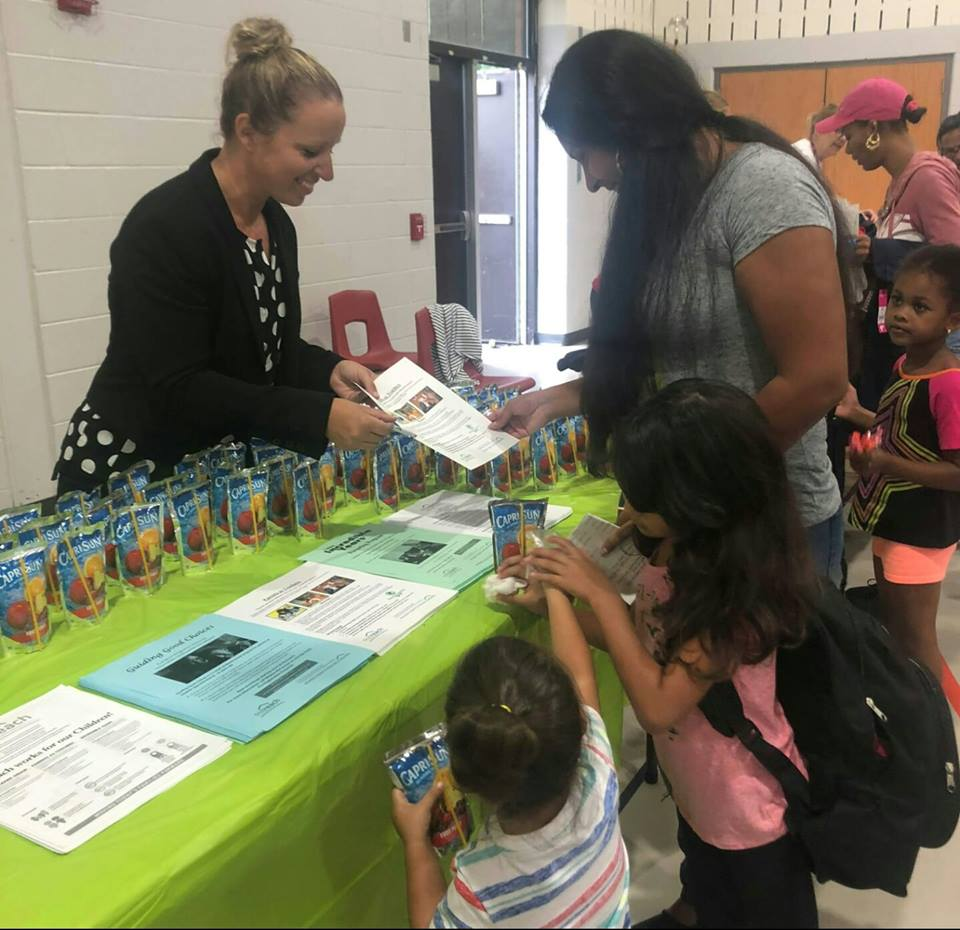 "Program Coordinator, Kristy Vassell, shares information about Outreach at a local ""Back to School"" fair."