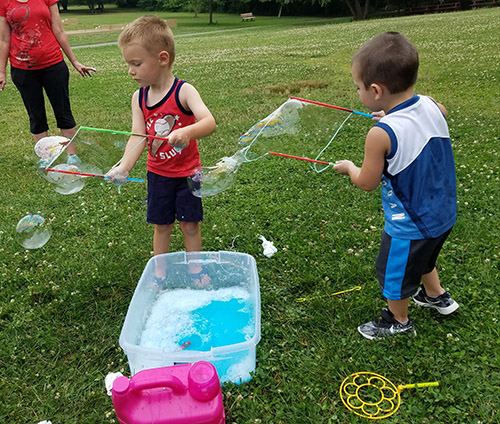 Children play with all of the donated toys, including these two enjoying new bubble wands.